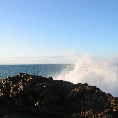 Brandung am Strand, der hier und da einen großen Felsen hatte